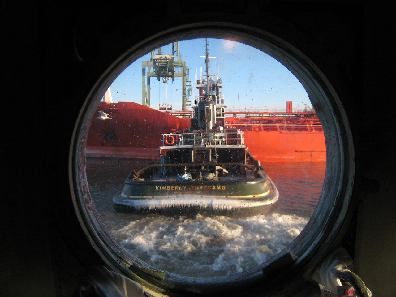 A dishwashing view of the Kimberly Turecamo tugboat docking a ship; note the stern ice—it takes a lot to freeze salt water