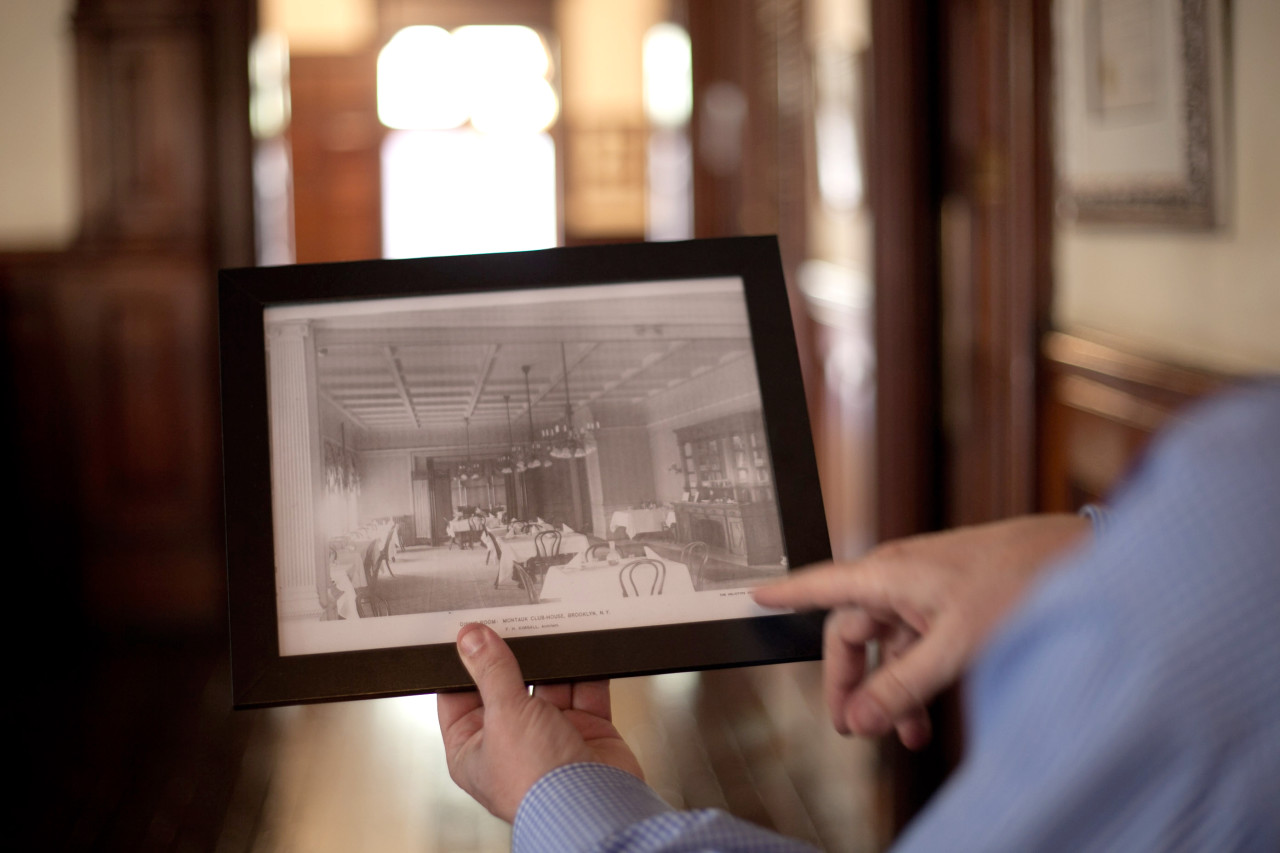 David Carter shows off a photo of the old dining room, now a condo located a floor above the current dining room.