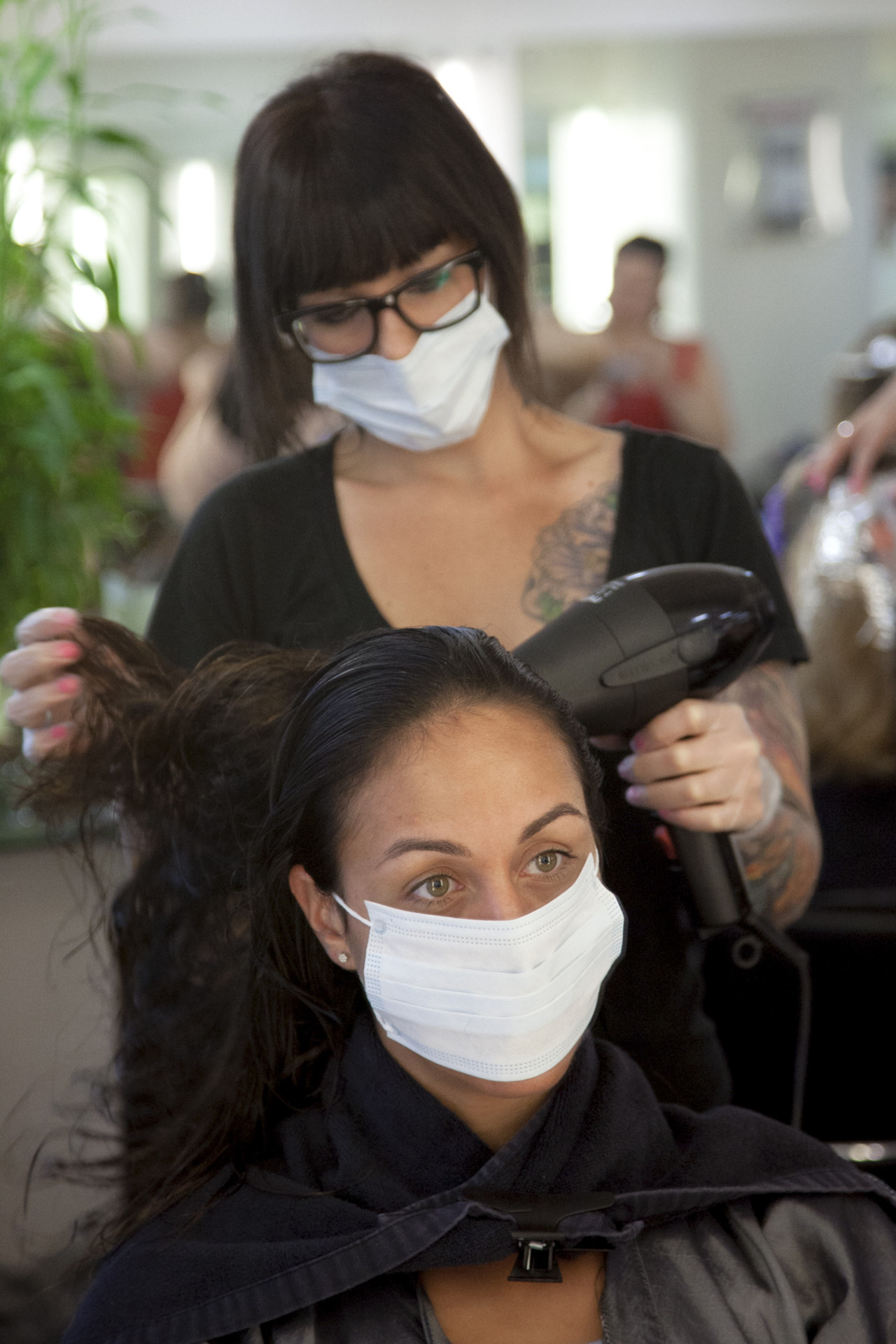 Keratin has to be sealed in with heat. To avoid inhaling the potentially dangerous fumes, both the hairdresser and client wear a face mask.