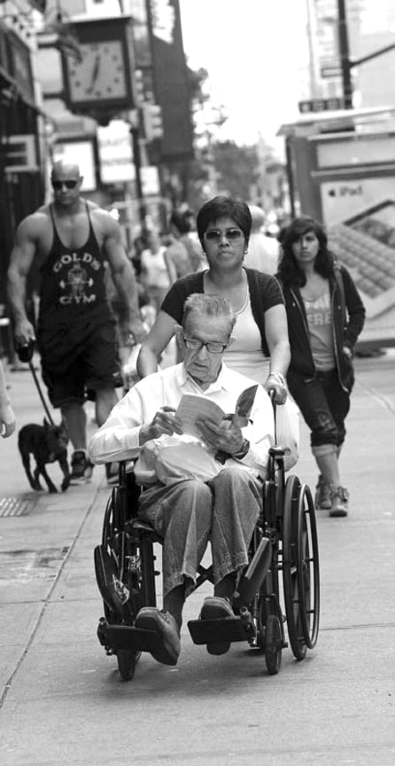 A man in a wheelchair reads a book while a bodybuilder walks his dog behind him on Amsterdam Avenue.