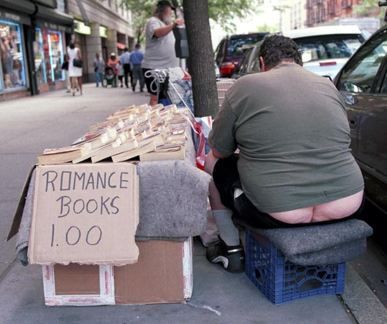 A street book vendor on the Upper West Side gets engrossed in one of his own books for sale.