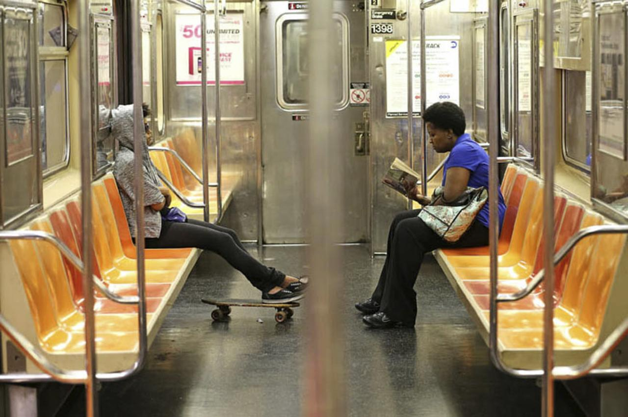 A woman reads a book on the #3 subway train.