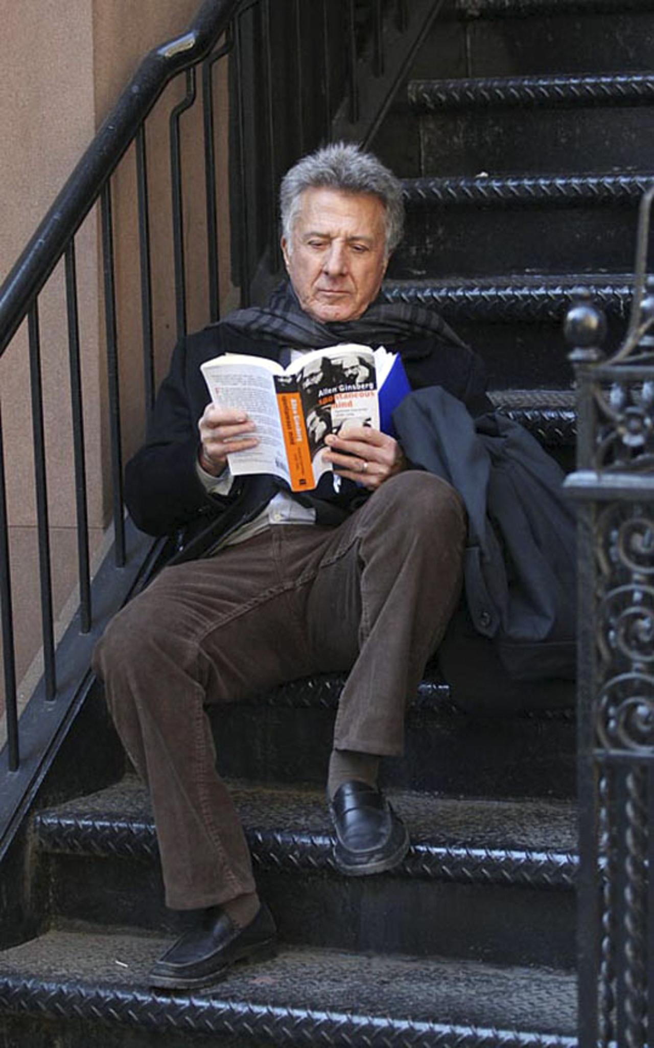 "Dustin Hoffman poses with a book of Allen Ginsberg's essays, ""Spontaneous Mind."""
