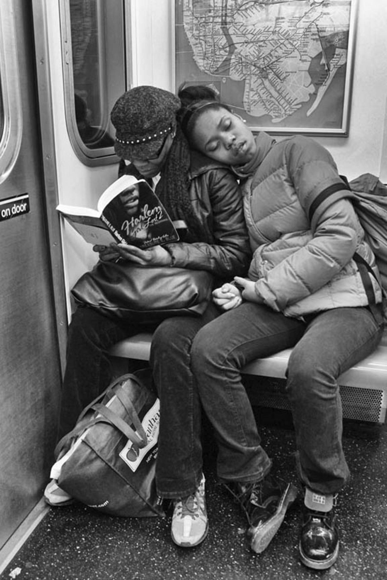 A woman reading on the #2 train while her daughter slumbers beside her.