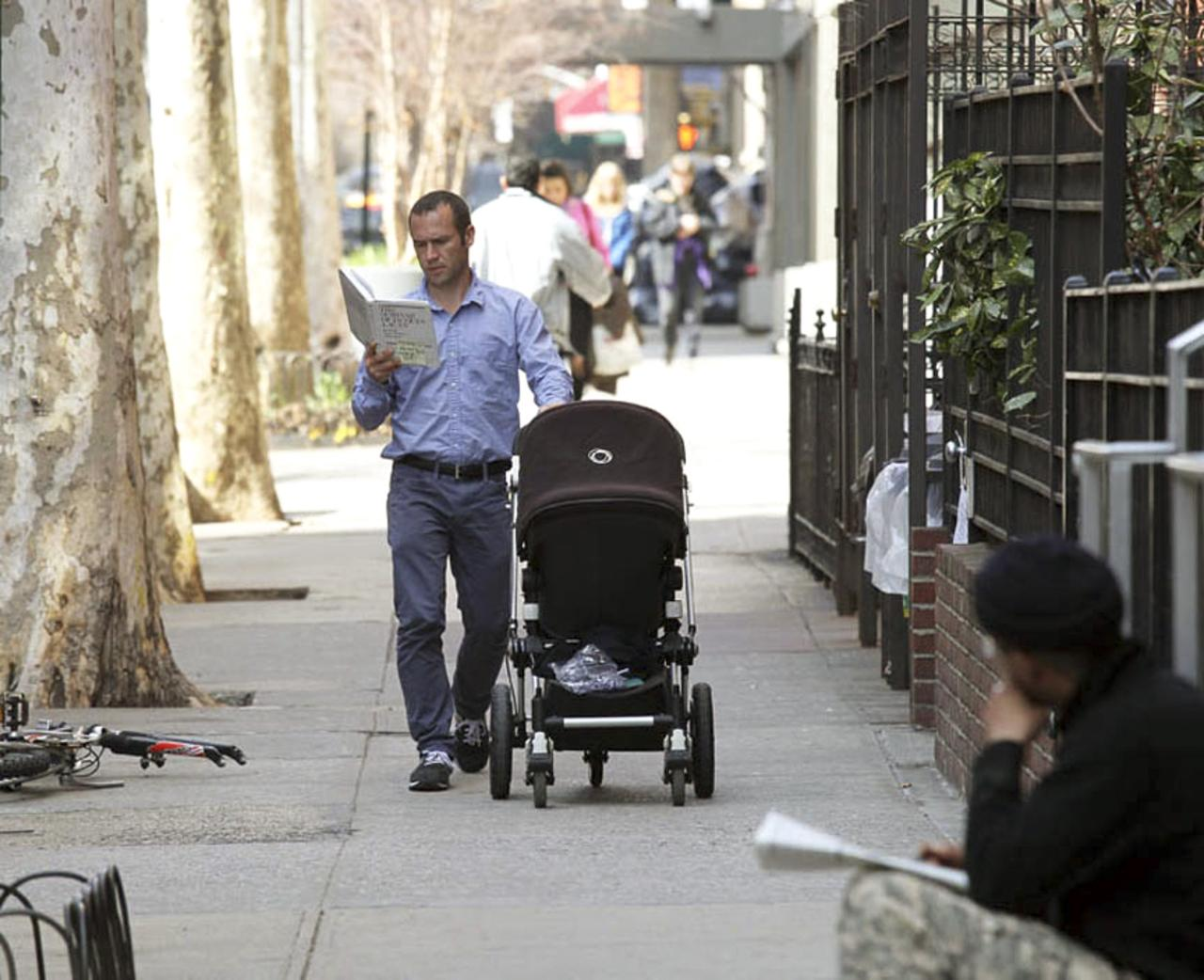 A man reads a book while pushing a stroller on 12th Street near Third Avenue.