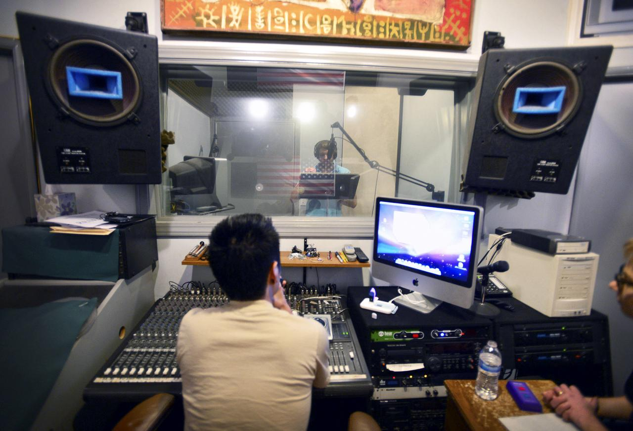 A student practicing inside the sound booth.