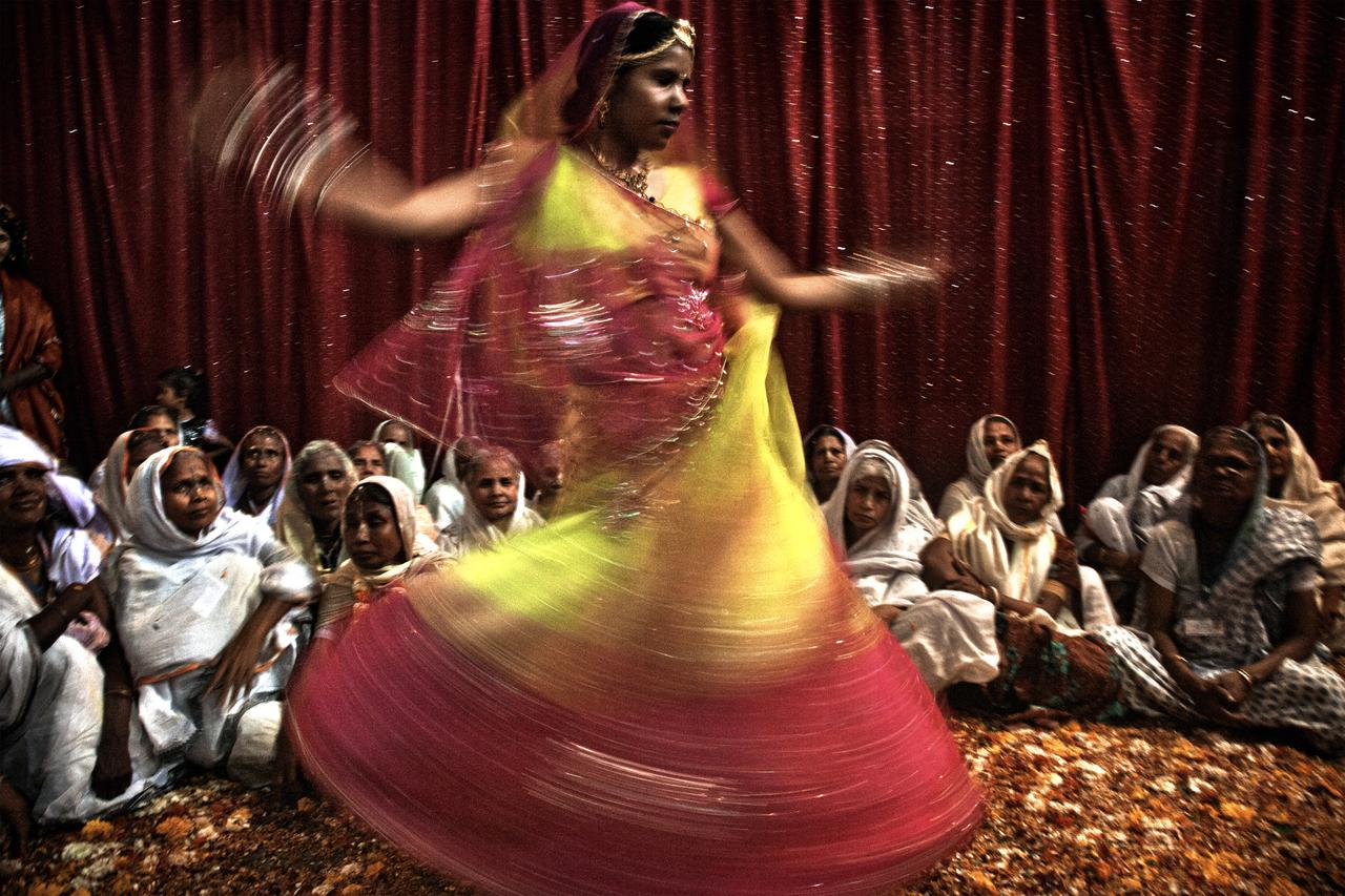 A dancer performs a show for an audience of fascinated widows in the ashram.