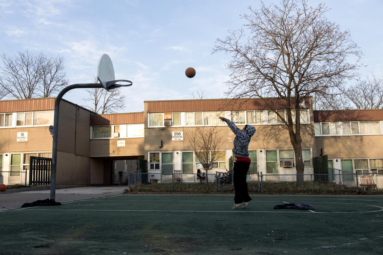 A child plays basketball on one of the courts in the townhouse complex known as The Lanes in the Jane and Finch area of Toronto.