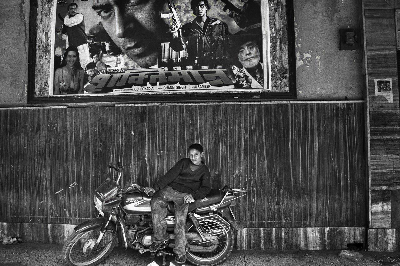 """Ajay, ten, posing on a motorcycle under the poster of """"Imperial"""" Cinema in Delhi. Ajay and his younger brother are orphans who come from the state of Bihar in northern India. They have lived on the rooftop of New Delhi Railway Station for about four years."""