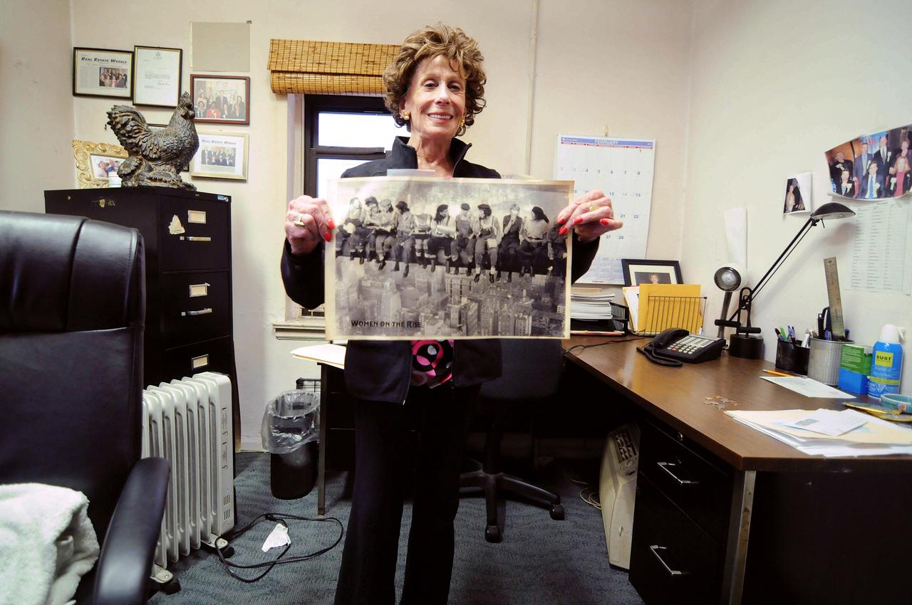 Lenore Janis, the president and owner of Professional Women in Construction, holds up an image of female workers which mimics Lewis Hine's famous photograph of men working on the Empire State Building.