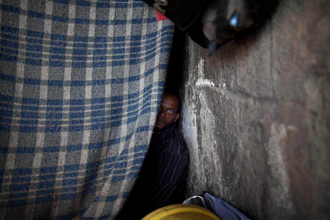 "A homeless crack user peeks out of his ""house,"" a shack made of wood and blankets and located under a bridge in São Paulo."