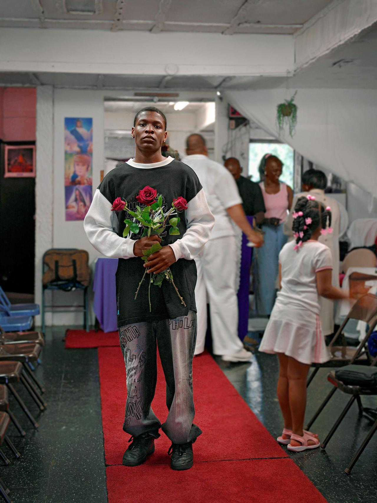 A young man holding blessed flowers at the Grace Miracle Temple.