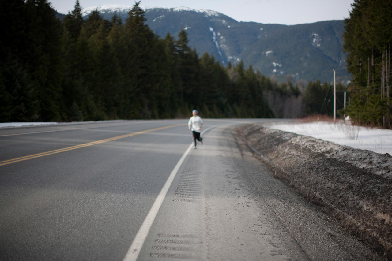 A woman runs along the Highway of Tears.