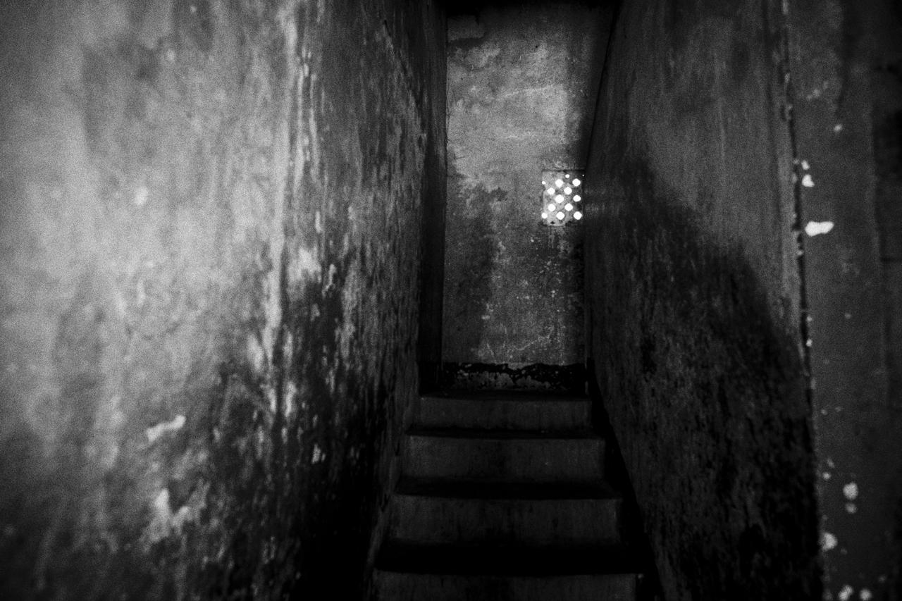 A dark and tight stairwell leads up to the house of the marabout in the back alleys of Dakar.