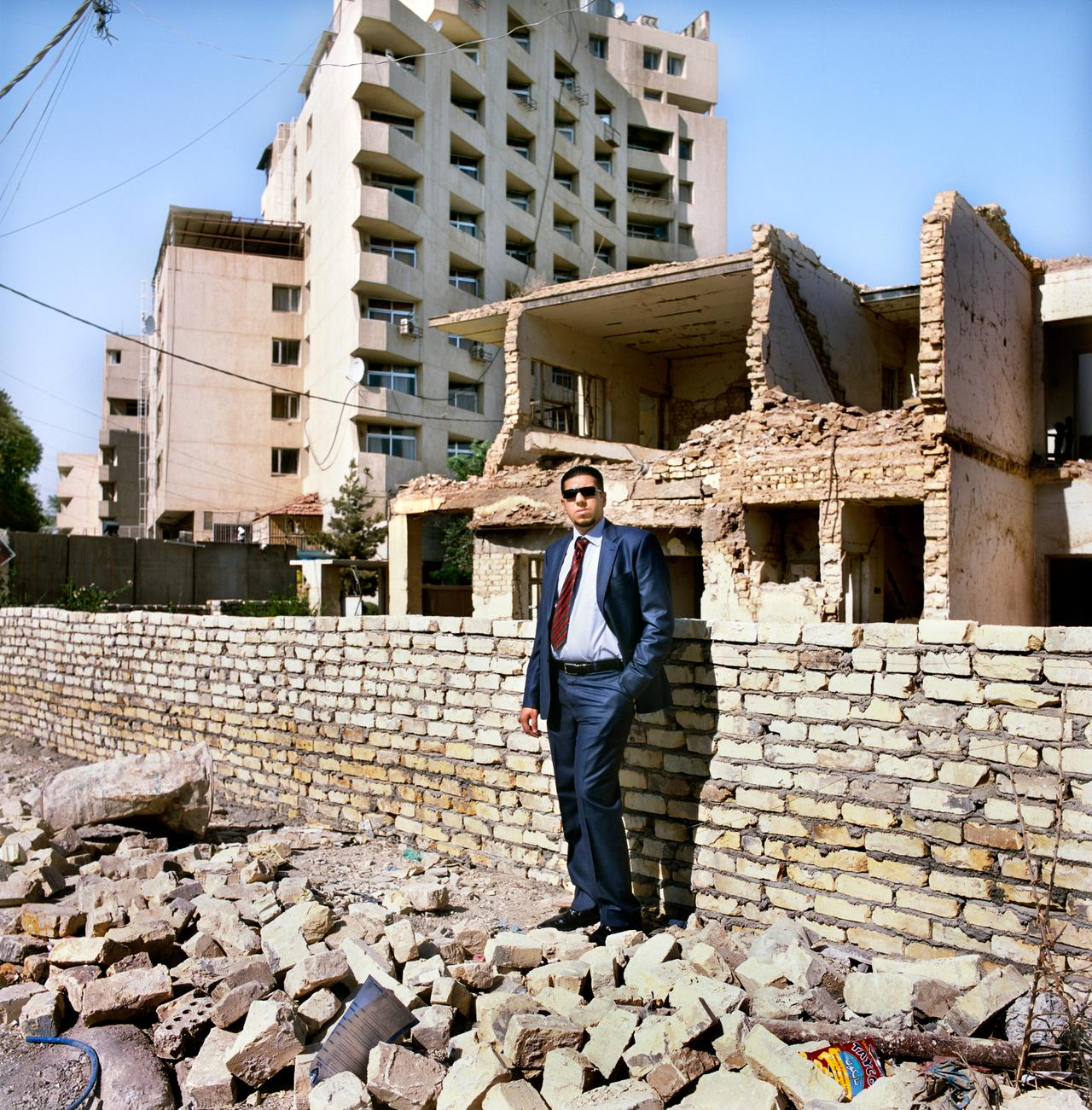 Firas in front of the remains of his uncle's house; Firas lives just to the right.