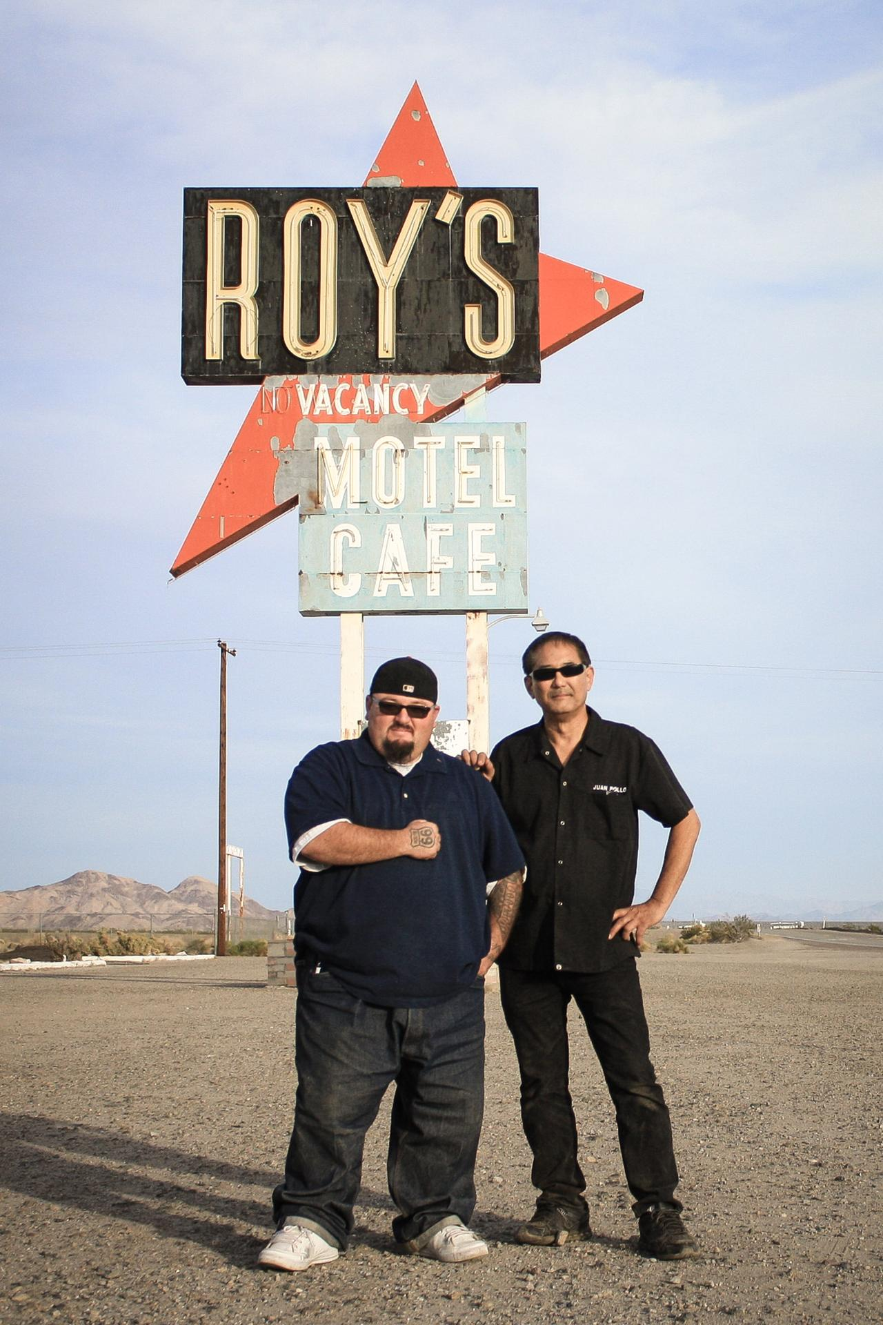 Charlie Aceves and Albert Okura stand in front of the historic Roy's Motel and Café sign. Okura, founder of the Juan Pollo chicken chain, bought the almost-ghost town of Amboy ten years ago and hopes to restore it to its former glory with the help of his righthand man, Aceves.
