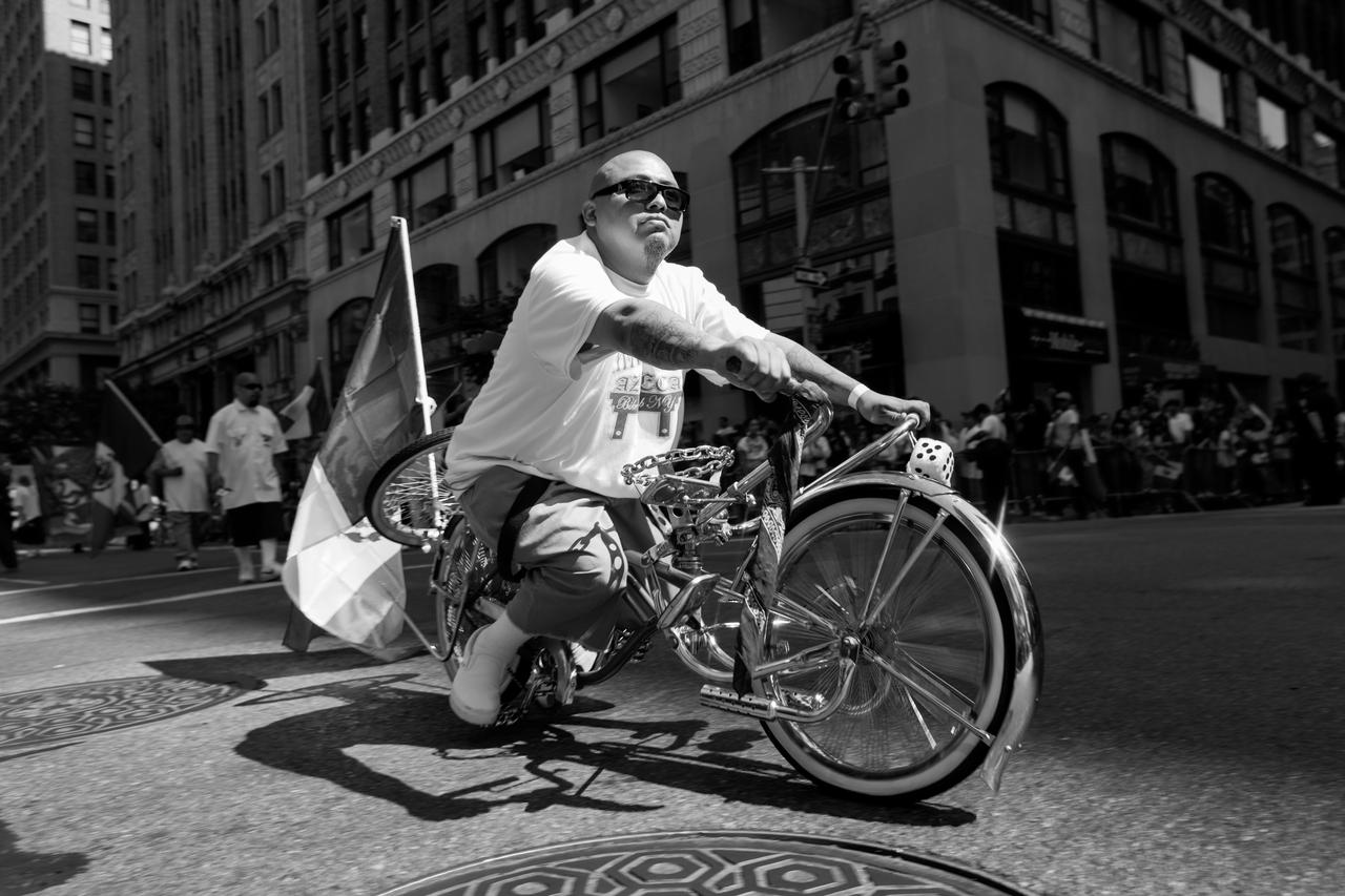 A member of the crew rides down Sixth Avenue in the Mexican Day Parade. Cholo culture has successfully ingrained itself in the Chicano and Mexican-American identity.