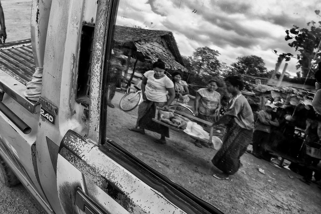 From the banks of the Moei River, Lae Lae (second from left) watches as her husband U Nay (right) and a friend carry Than Zin Moe on a bamboo stretcher to a truck to transport them to the Mae Tao Clinic.