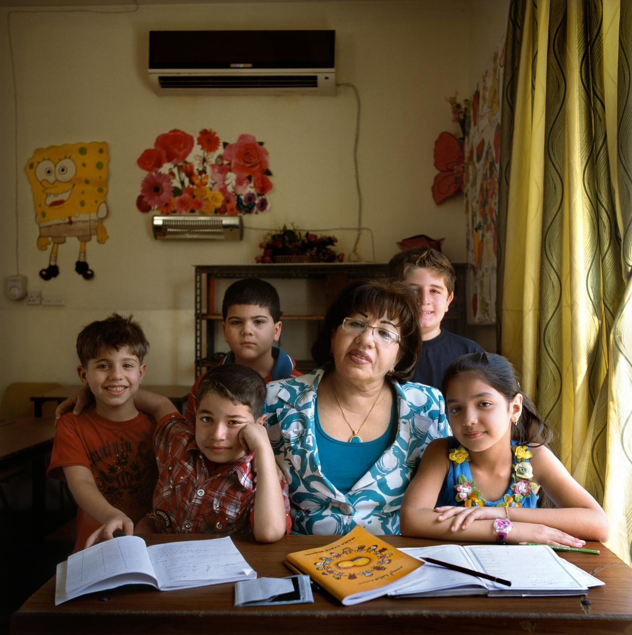 A portrait of Mama Ayser in one of the classrooms, in between some of her young Iraqi students.