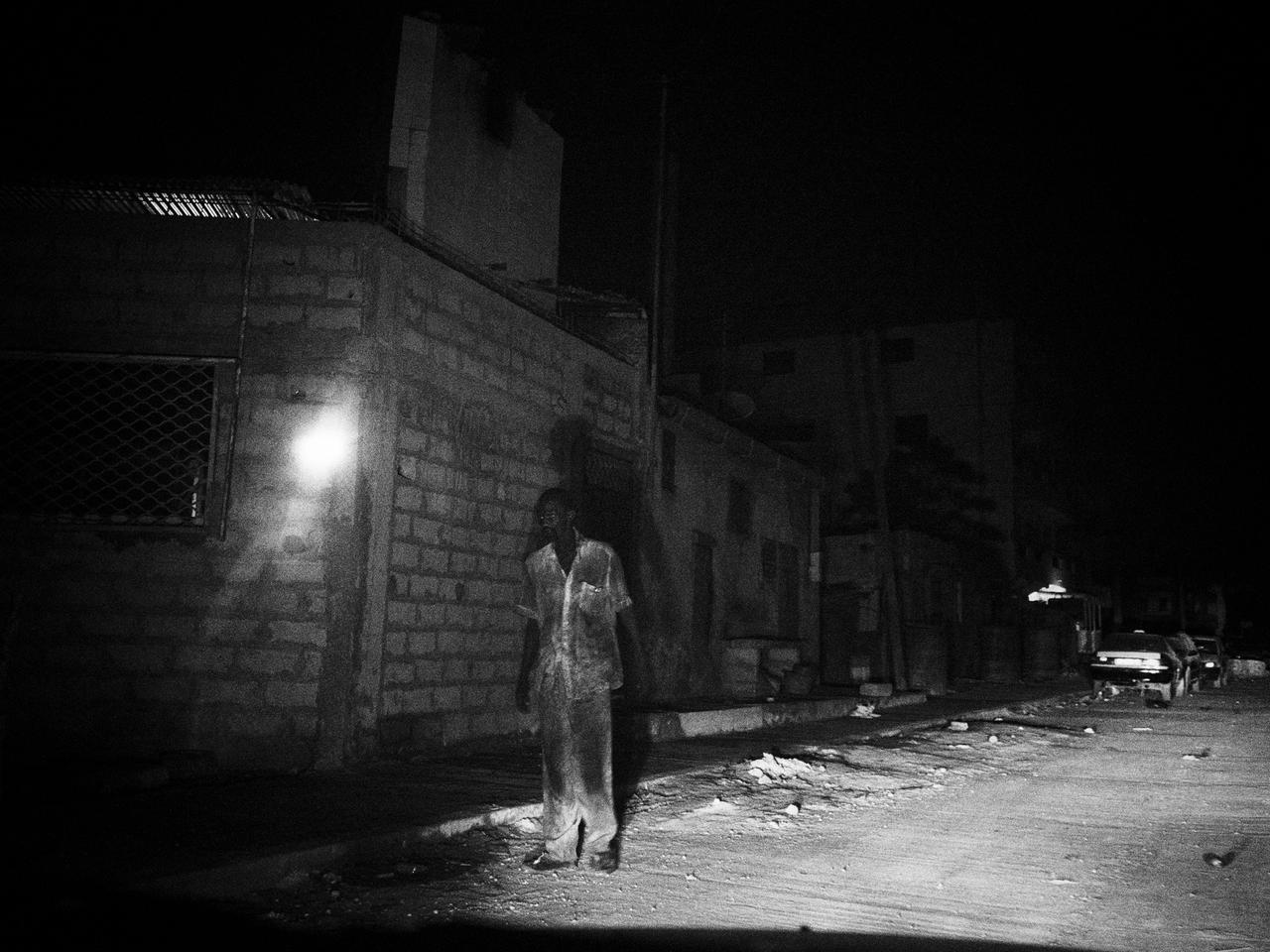A dark alley in Dakar lit by the high beams of a passing car, near the house of the marabout.