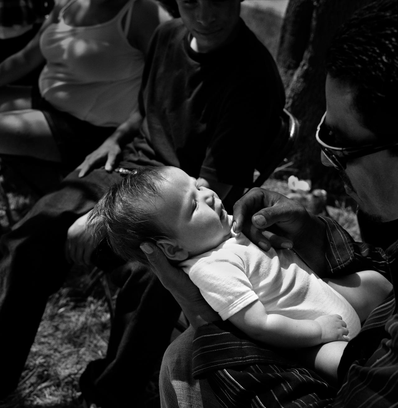 The Sanchez family holds their newborn brother at a Walden House picnic in Los Angeles, California. Their mother, Yvette, has just had her baby in prison. The Sanchezes said they hoped for the family to grow stronger once Yvette is off parole.