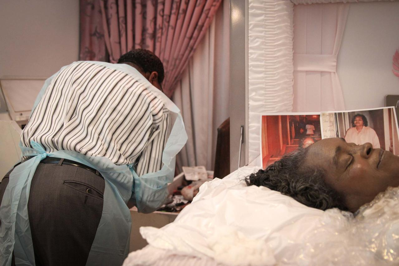 Owens looks for some make-up. In the casket, he keeps some pictures the family gave him as a reference to achieve the right look.