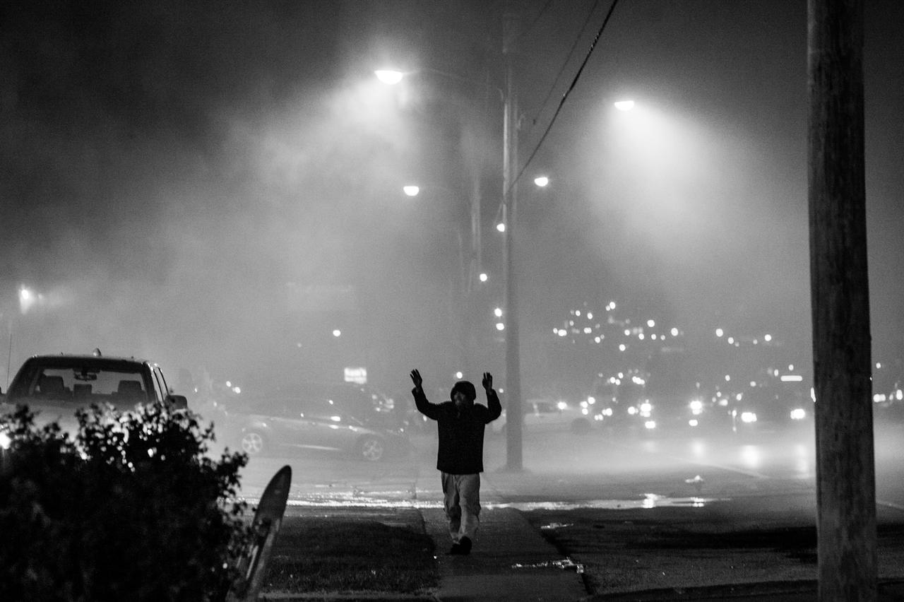 A man walks down West Florissant Avenue with his hands up during the rioting.