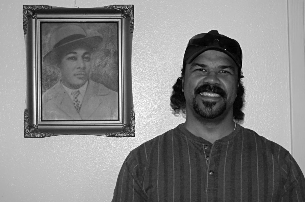 Clifton Walker Jr. stands in front of a portrait of his father.