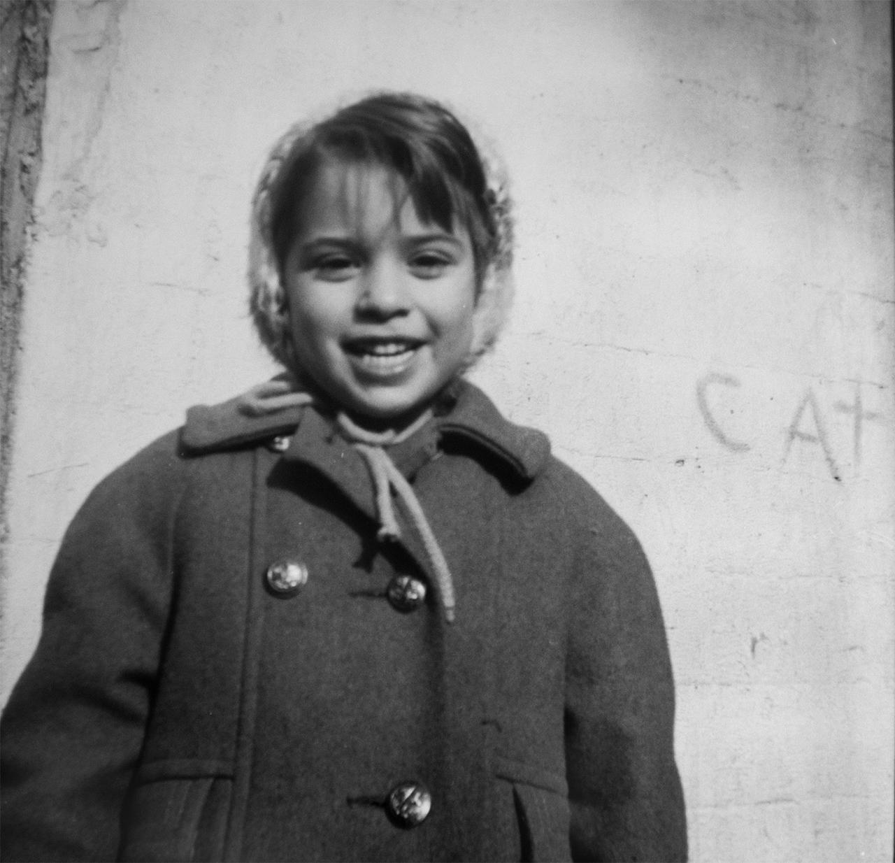 "Debi Romano in 1964, at the age of five. Behind her is the word ""cat,"" which she wrote on her family home."