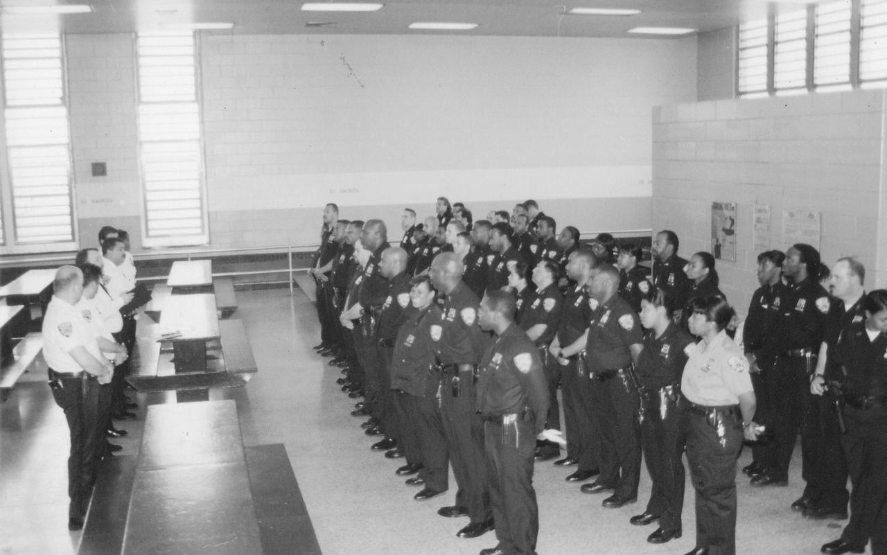"Correctional officers gather for roll call at what was then called the Adolescent Recession Detention Center (ARDC), which held 14-to 21 -year-olds on Rikers Island. When Lorenzo Steele became an officer in the late 1980s, he spent two to three months in the academy before being assigned to ARDC. ""They could never prepare you mentally and physically for what you were about to experience,"" Steele told Pete Brook. Steele spent 12 years as a New York City corrections officer. ""One of the blessings was that I always had good supervisors,"" he said. ""When the captain said 'go', you went, and when he said 'stop', you stopped. You put your life in the hands of your captain; it's almost like being in a war."" (Lorenzo Steele Jr.)"