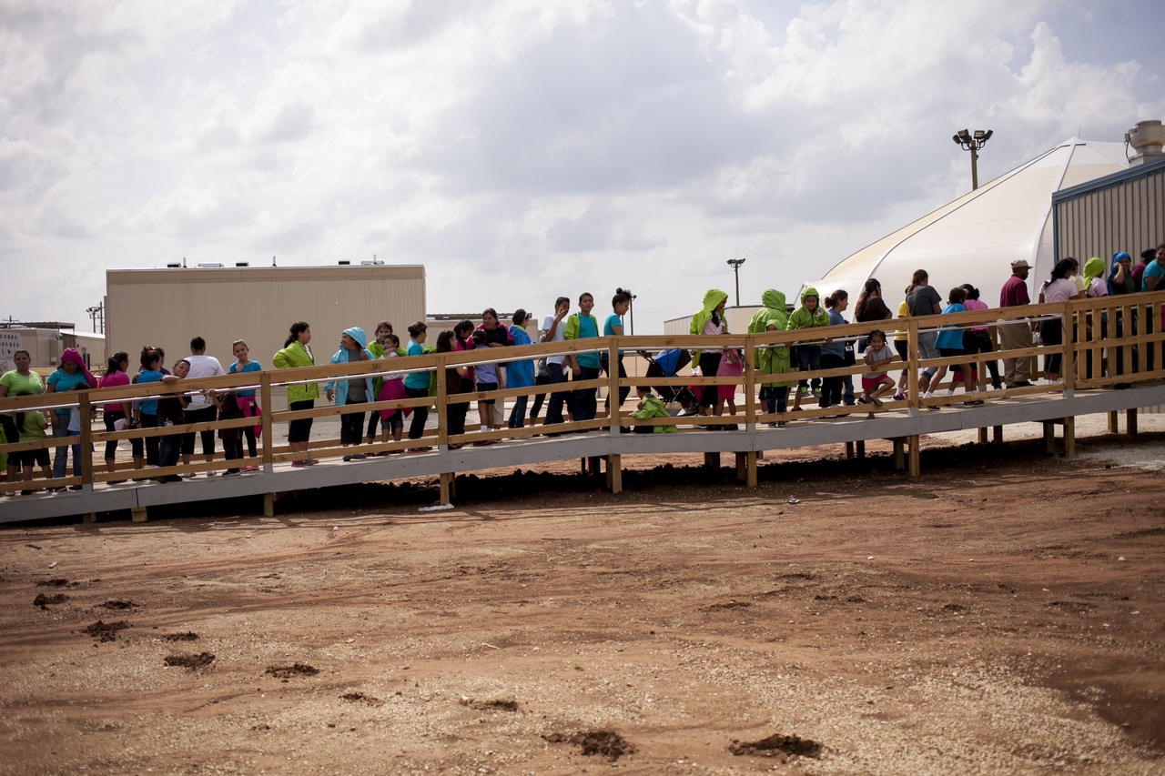 Residents walk through the facility grounds to eat lunch at the cafeteria. Built to hold up to 2,400 women and children who are seeking asylum, the Dilley facility is the largest of its kind, and while residents may move freely from building to building, they are not permitted to leave the grounds.