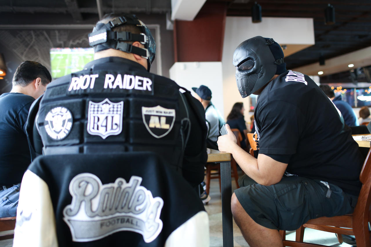 "205444dfafa Two members of the ""66th Avenue MOB"" group of Raiders fans watch the 2015"