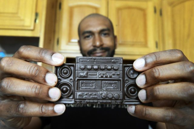 "Marcus Gray, founder of Hip Hop Chocolate, holds up the ""Ghetto Blaster,"" one of his signature creations at his home in Los Angeles Wednesday.   Photographs of Marcus Gray, founder and owner of Hip Hop Chocolates at his home in Los Angeles Wednesday March 19, 2014."