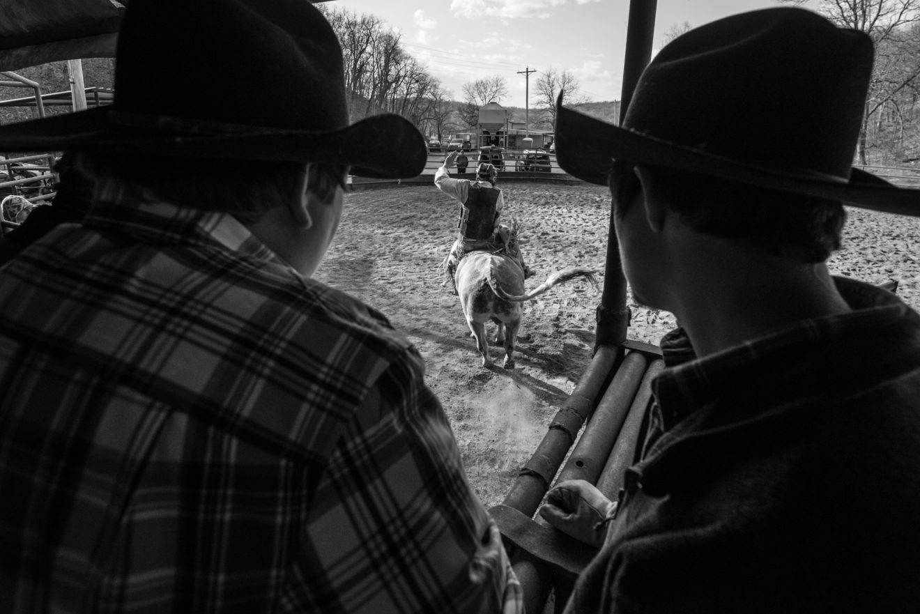Young cowboys watch as a fellow student rides his first bull.