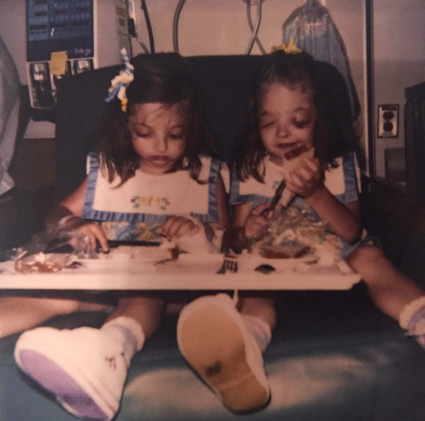 Ariel and her twin sister, Alixandria, five, eating bread in the hospital.