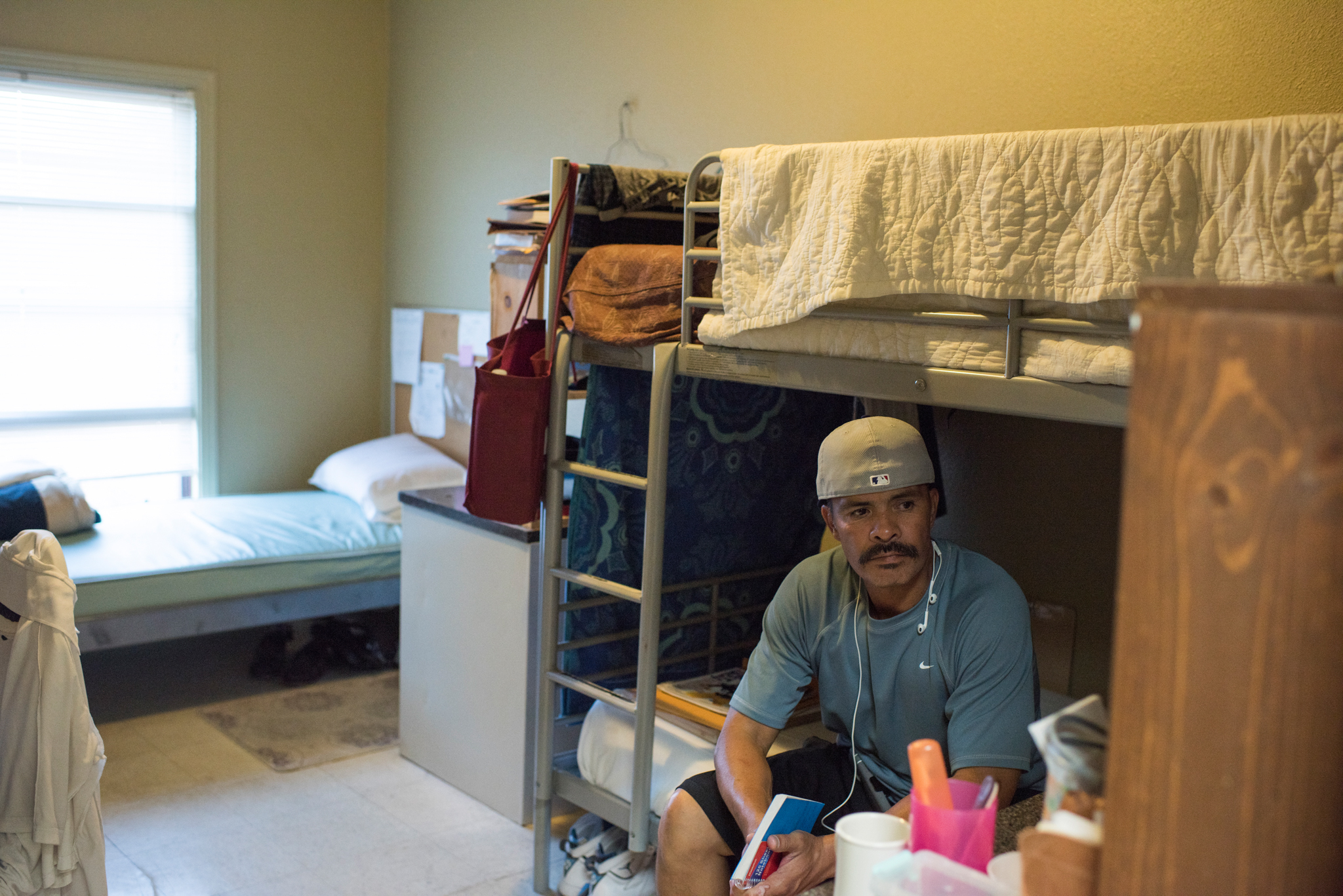 Ricardo sits in his room that he shares with two other formerly incarcerated men.
