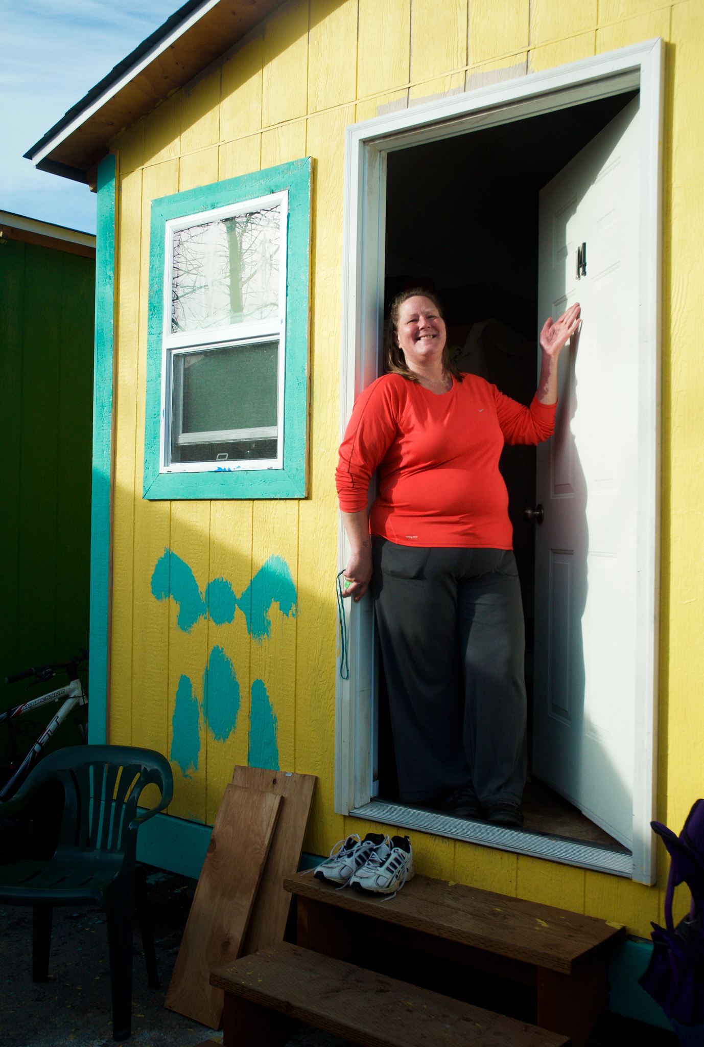 Mitze Buffer stands in the doorway of her tiny home at Seattle's Othello Village. Having spent six years sleeping in a tent before coming to Othello, Buffer says she was so unused to a private dwelling that during her first week she locked her keys into her tiny home three separate times.