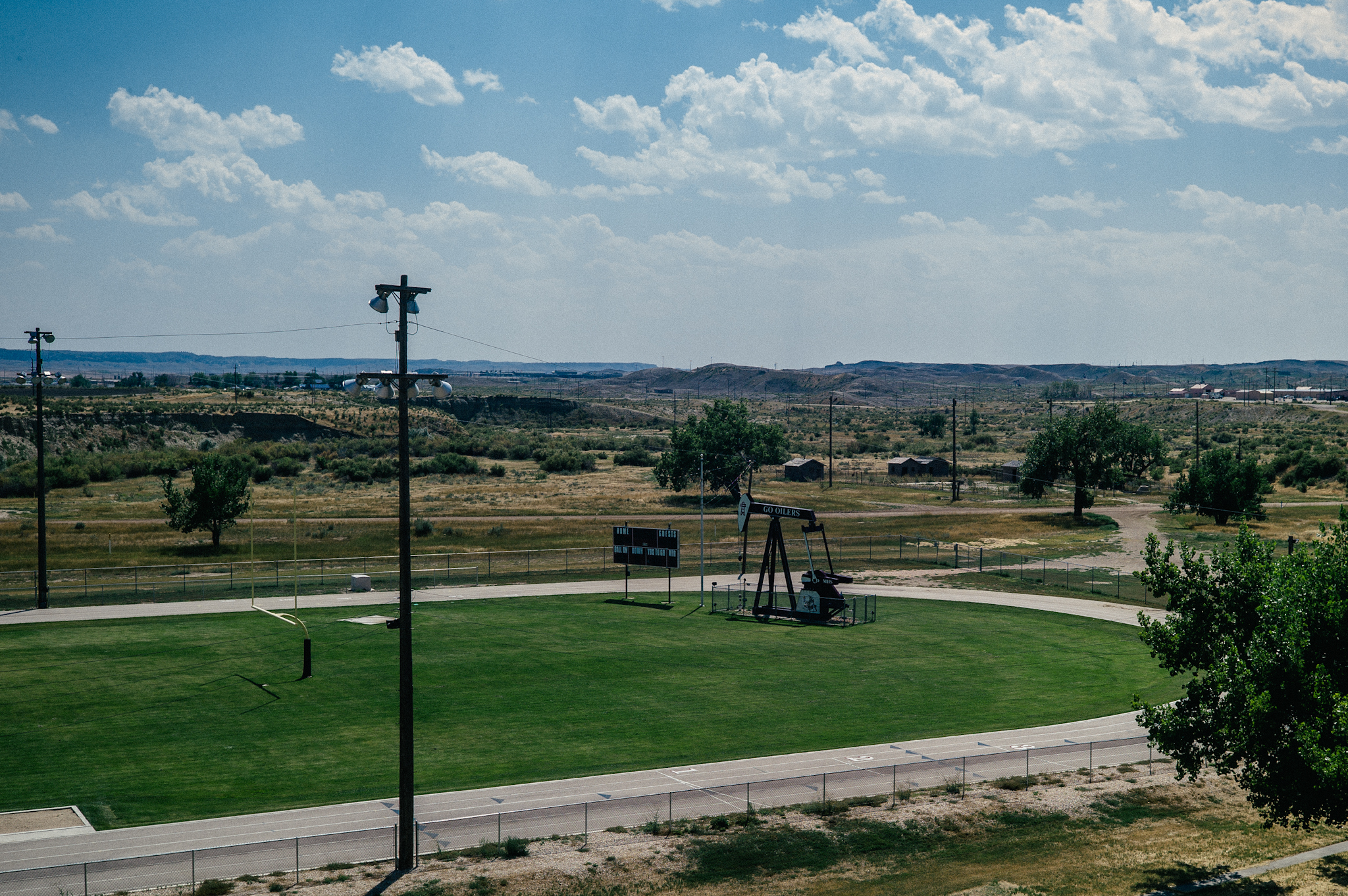An oil pad stands on a high school track field in Midwest, Wyoming.
