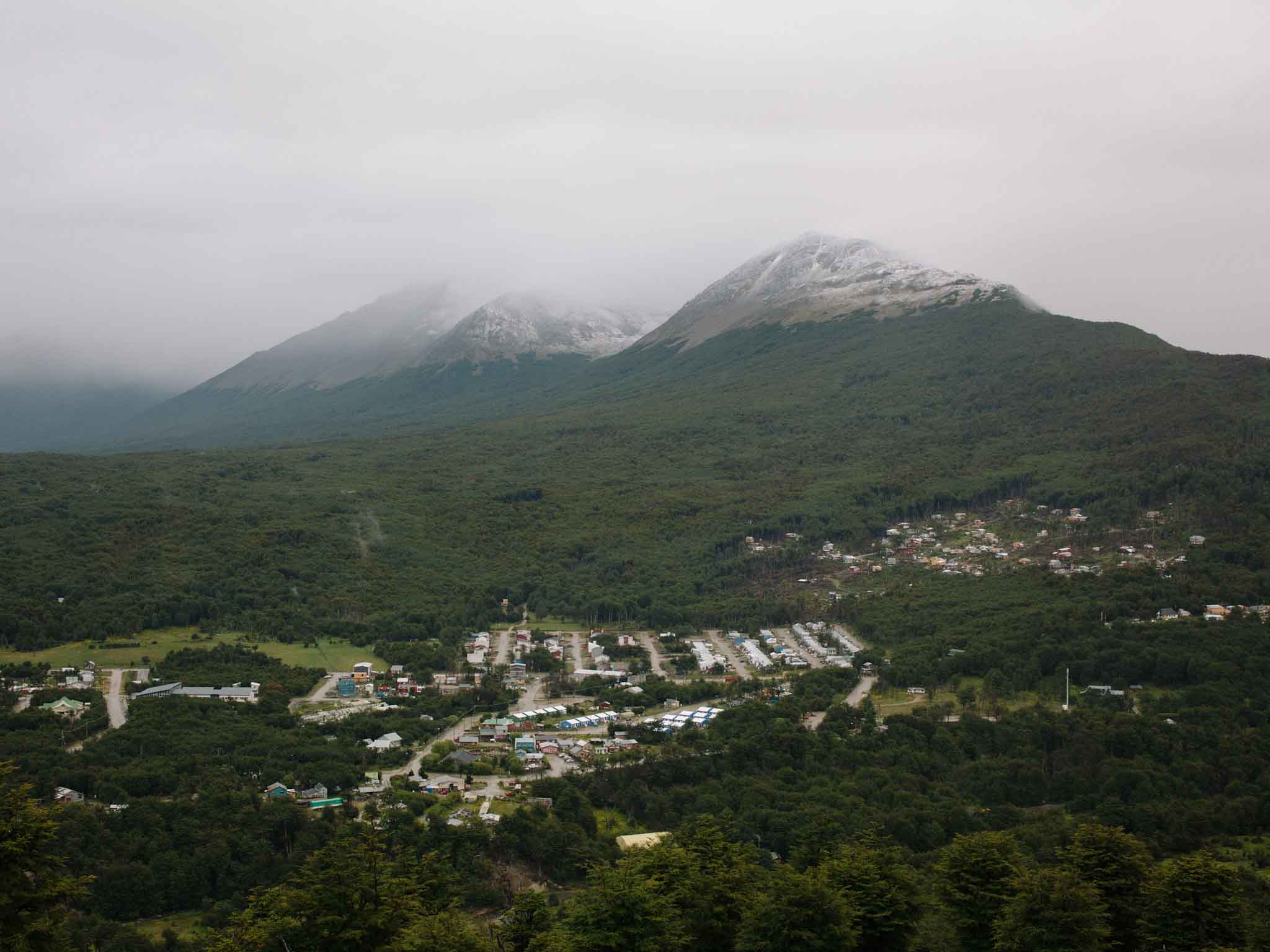 A view of the Andorra district of Ushuaia, pictured in the foreground. Andorra is another occupied district neighboring Dos Banderas, which can be seen on the wooded slope in the background.