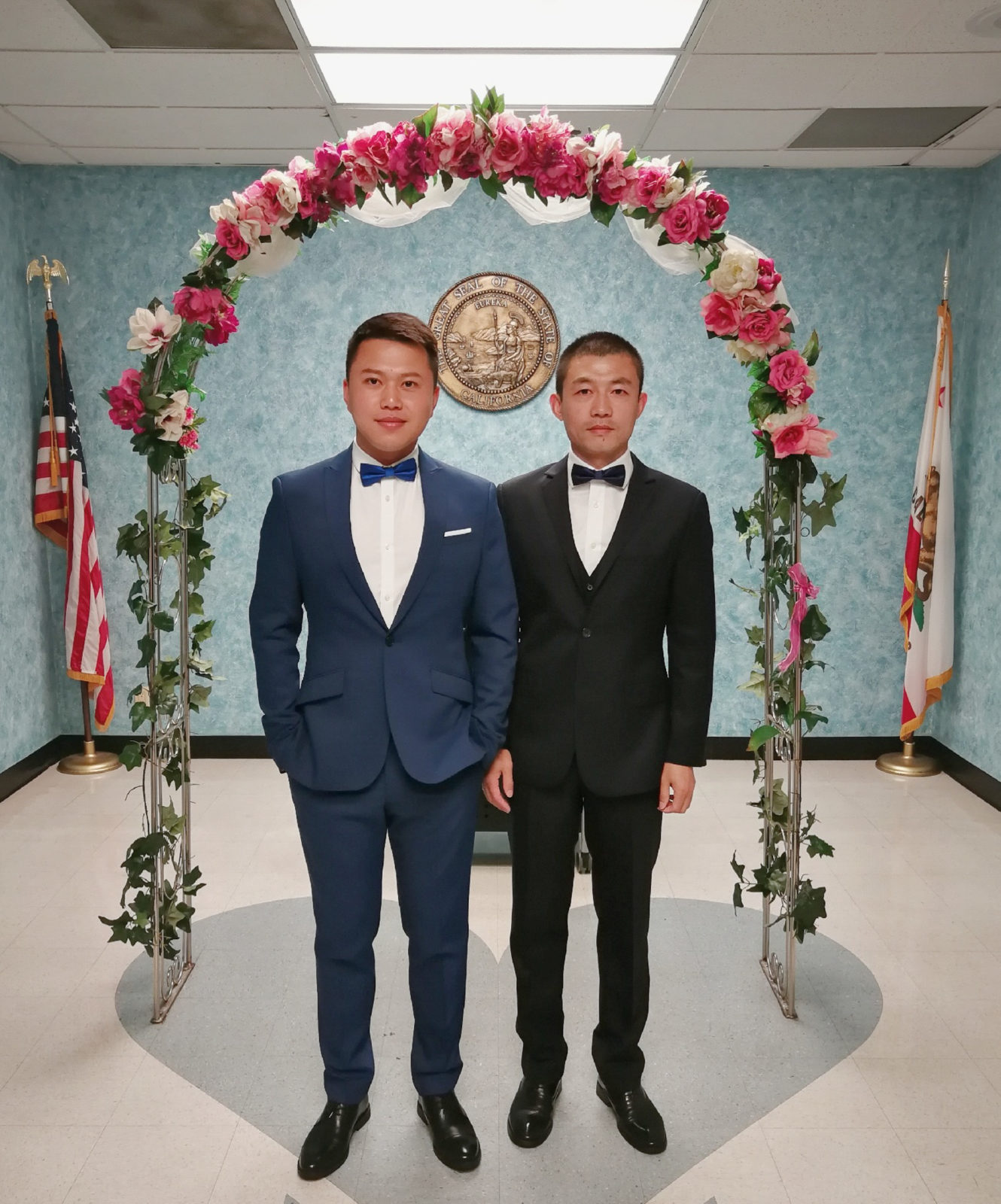 Two men in suits stand under an arch made of flowers. It is their wedding day.